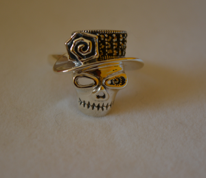 """bague tête de mort, en argent massif, décorée d' accessoires, dont un chapeau, une rose, et ornée de pierres semi-précieuses, très """"gothique""""."""